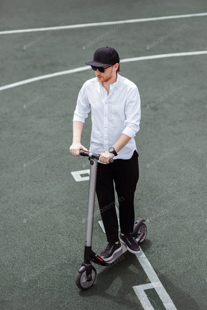 Modern man in stylish black and white outfit riding electric scooter in the city