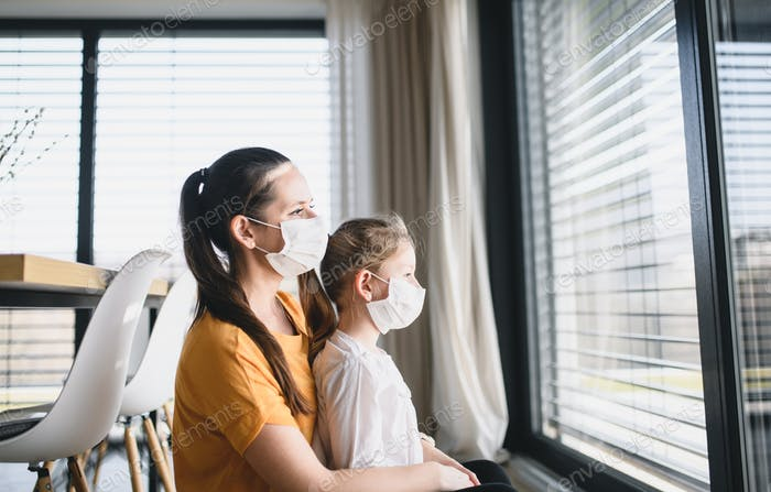 Mother and child with face masks indoors at home, Corona virus and quarantine concept