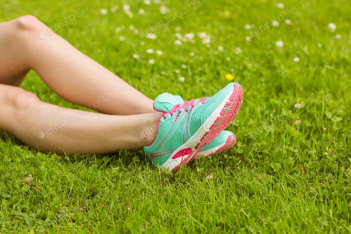 Woman in running shoes lying on grass in the park