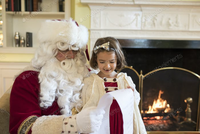Little girl asking Santa for gifts at Christmas