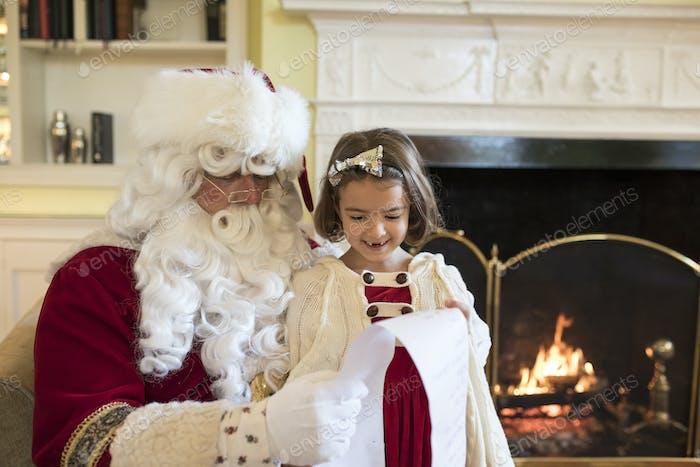 Kleines Mädchen, das Weihnachtsmann um Geschenke zu Weihnachten bittet