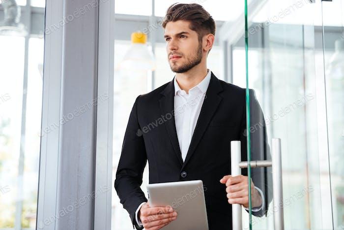 Бизнесмен держит планшет и войдя в дверь в офис