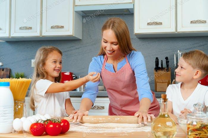 Madre y sus hijos pequeños, niño y niña, ayudándola a preparar la masa