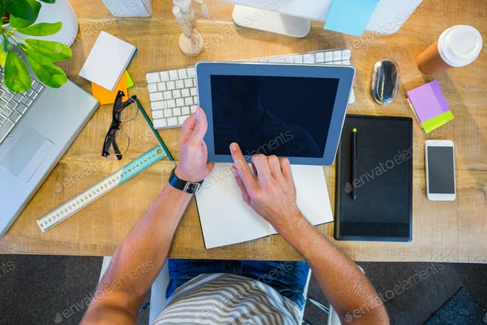 Casual businessman working on tablet at his desk