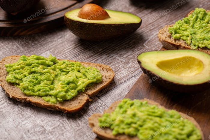 Avocado sandwiches next to cutted ones on wooden board