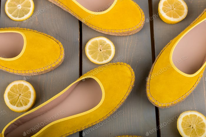Yellow espadrilles shoes near slices of lemon