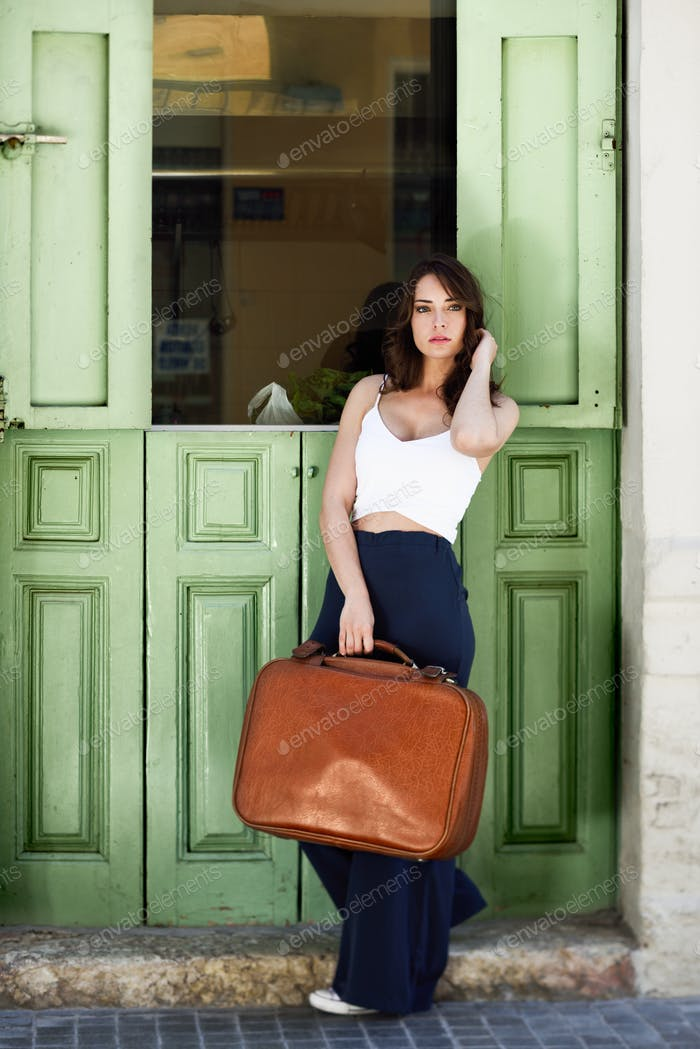 Beautiful girl with vintage bag against green door
