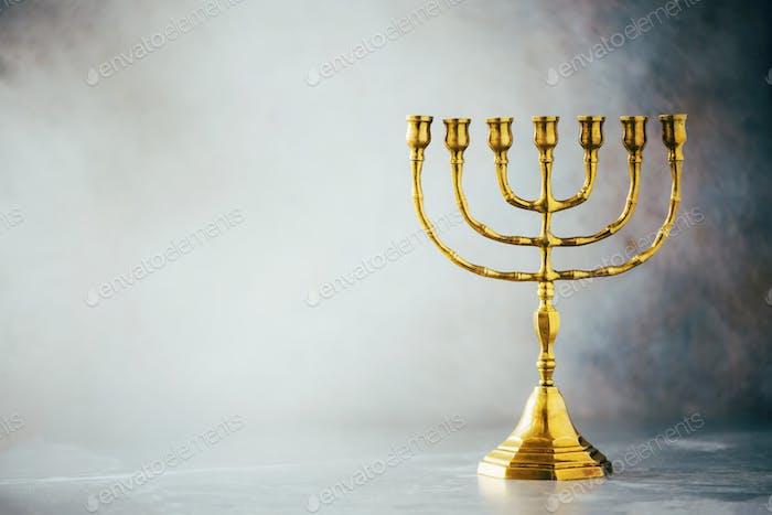 Goldene Chanukkah Menora auf grauem Hintergrund. Jüdisches FeiertagBanner mit Kopierraum. Antikes Ritual