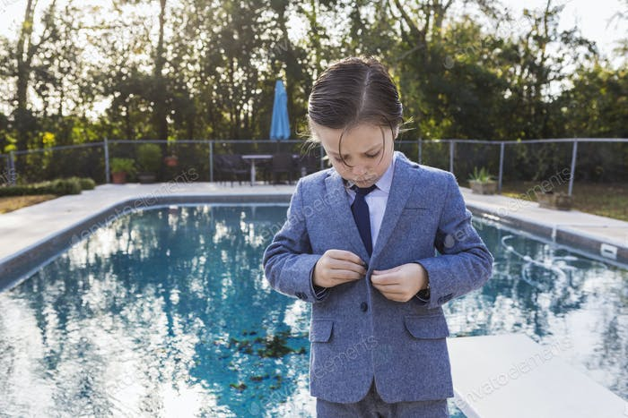 6 year old boy buttoning  his suit with pool in background