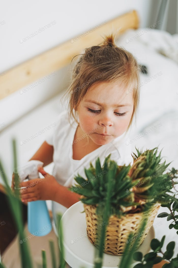 Funny cute toddler girl watering house plant at room
