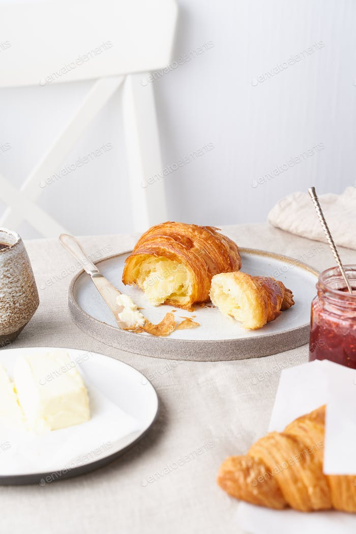 Coffee with croissant. Traditional french breakfast. Bright sunny morning, vertical