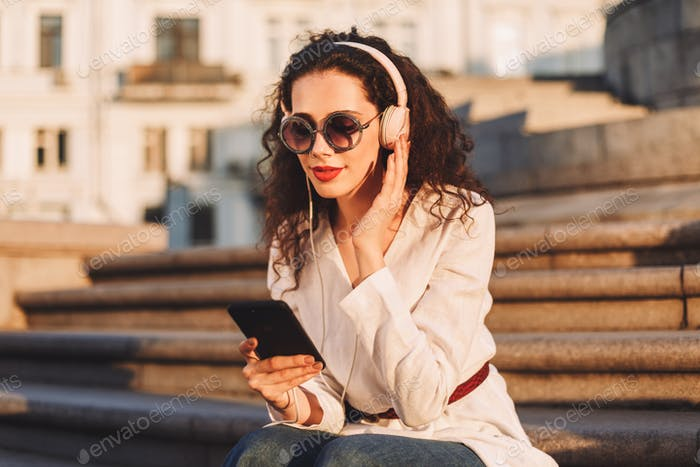 Pretty girl in sunglasses and white jacket sitting on stairs listening music in headphones on street