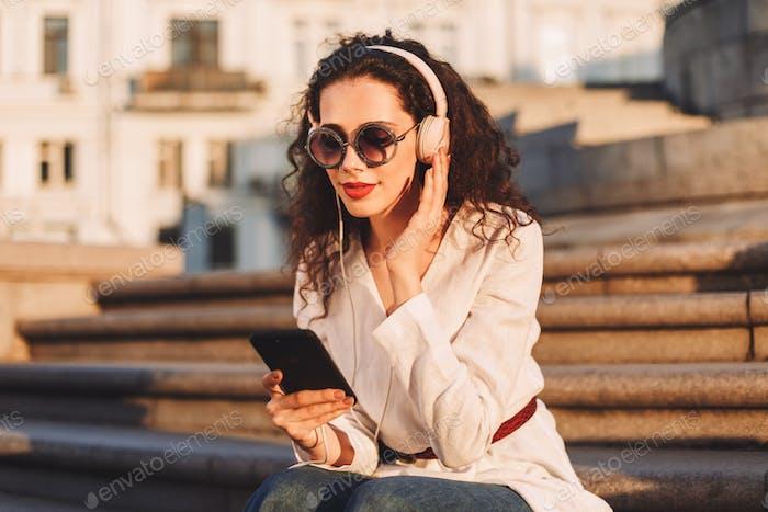 Chica bonita en gafas de sol y chaqueta blanca sentada en escaleras escuchando música en auriculares en la calle
