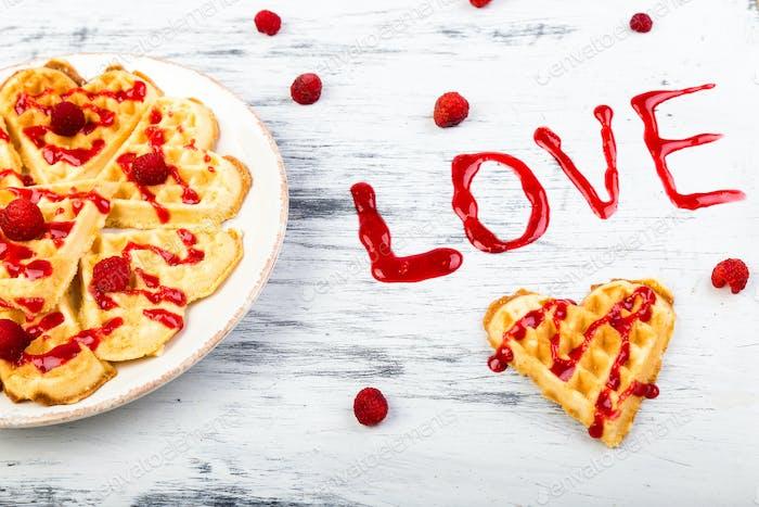 Belgische herzförmige Waffel auf weißem Hintergrund. Wort-Liebe gemacht durch Marmelade.
