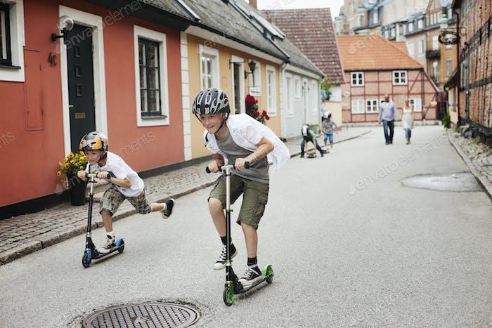 Glückliche Jungs reiten Push-Scooter auf der Straße in der Stadt