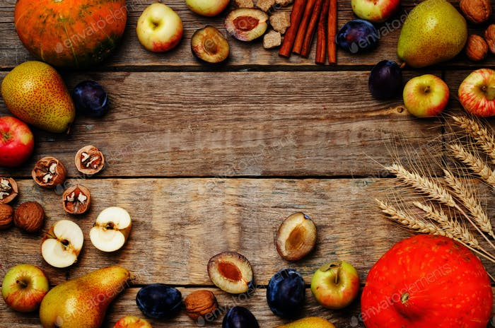 autumn wood dark background with pumpkin, fruit, nuts and wheat