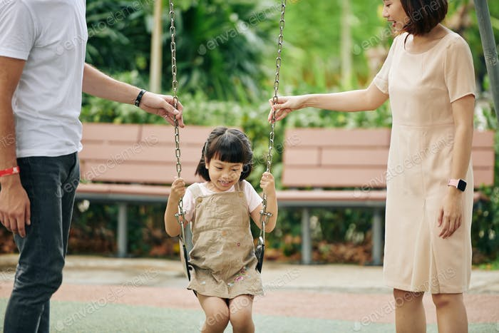 Parents pushing daughter on swing