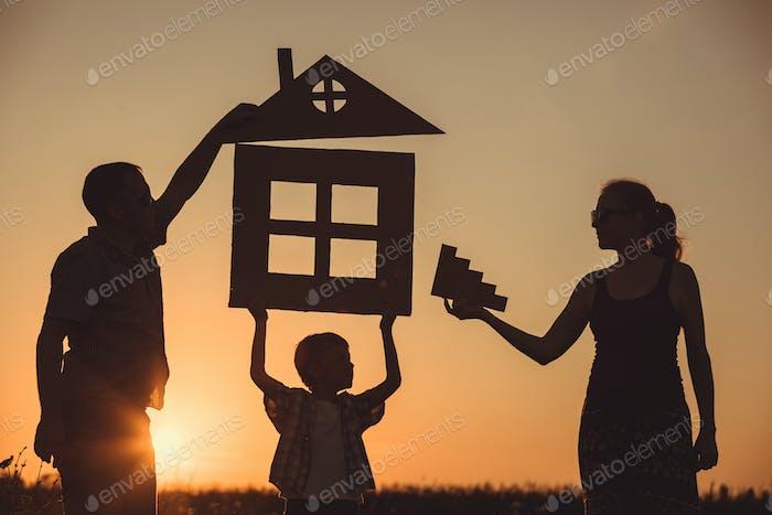 Glückliche Familie steht auf dem Feld bei Sonnenuntergang Zeit.