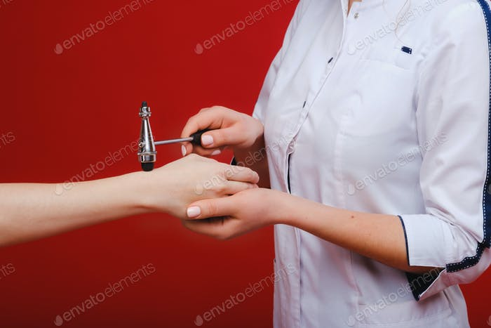 The doctor is holding a neurological hammer on a red background. The neurologist checks the patient