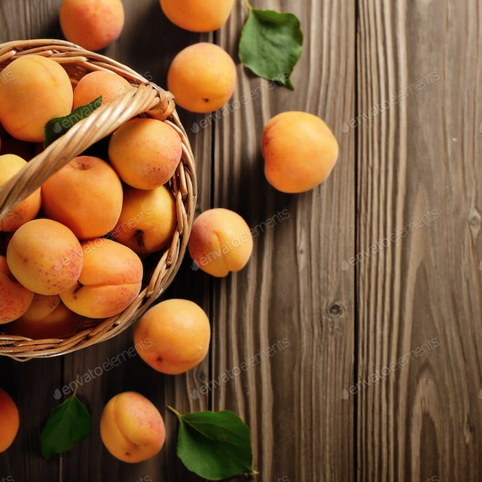 Top view of Wicker basket with ripe apricots on wooden table. Pl