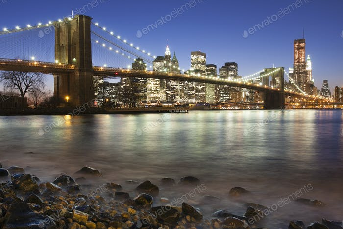 Night view towards Manhattan from Brooklyn, with the Brooklyn Bridge spanning the East River.