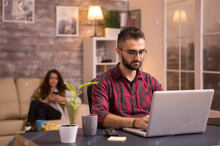 Bearded freelancer working on laptop in living room