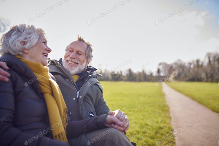 Liebendes Seniorenpaar sitzt auf dem Sitz und genießt zusammen einen Herbst- oder Winterspazier