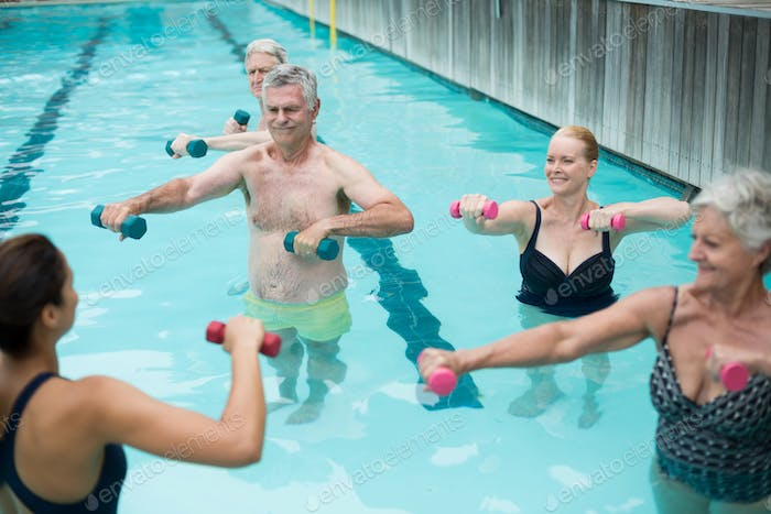 Senior swimmers and instructor lifting dumbbells in swimming pool