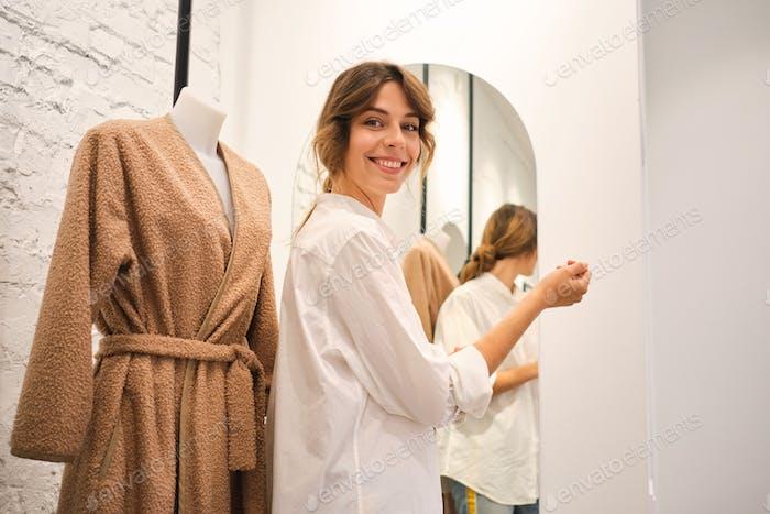 Junge hübsche Frau glücklich arbeiten in der Kamera während der Arbeit in der Werkstatt auf neue ModeSammlung