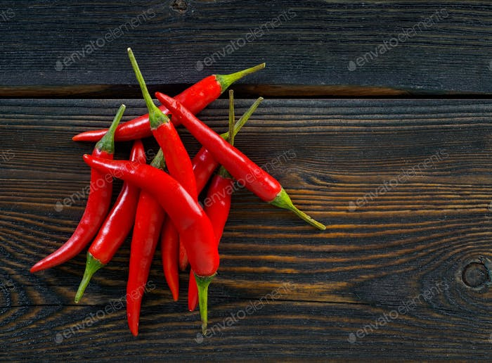 Red hot chili pepper on dark wooden background, top view, copy space