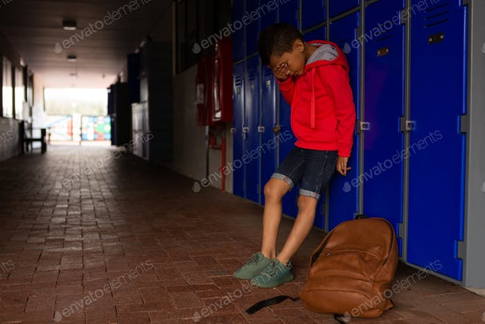 Sad schoolboy standing alone covering his face with his hand in corridor at elementary school