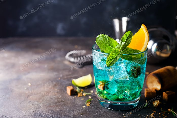 Blue cocktail in glasses with ice, mint and orange