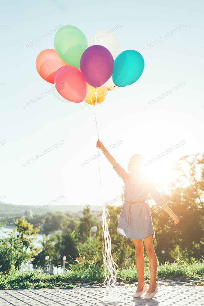 Girl holding colorful balloons stretching to the sky