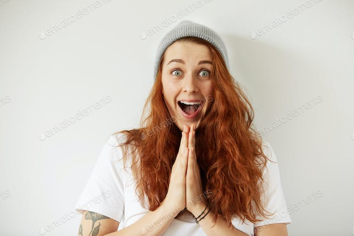Close up isolated portrait of young female with long loose red hair looking in excitement at the cam