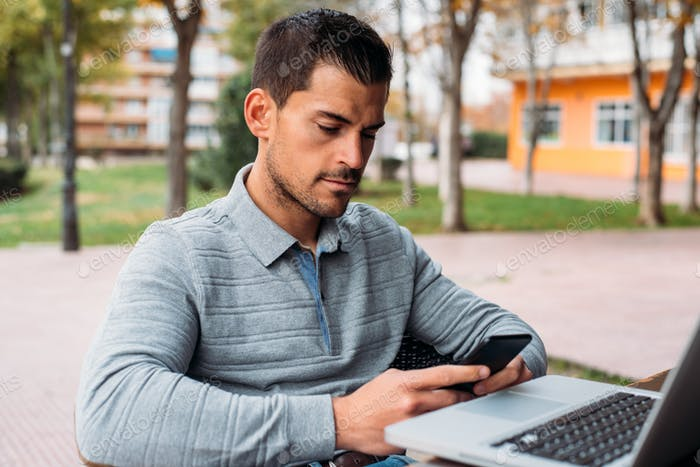 Young man with mobile phone and computer