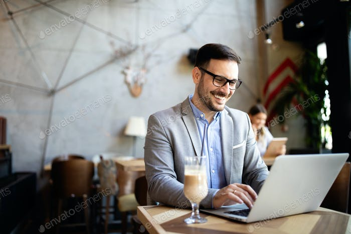 Happy confident businessman working, using laptop in office