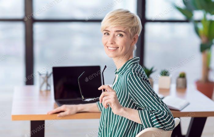 Smiling Businesswoman Posing Holding Eyeglasses Sitting In Office