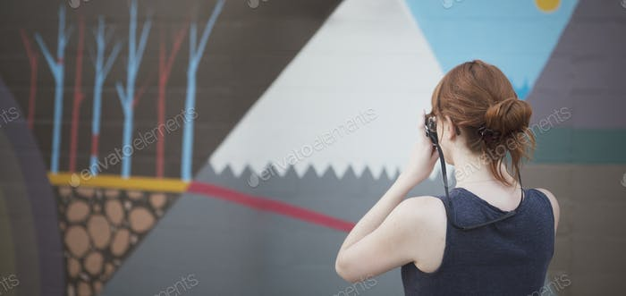 Woman Taking a Photo of a Mural