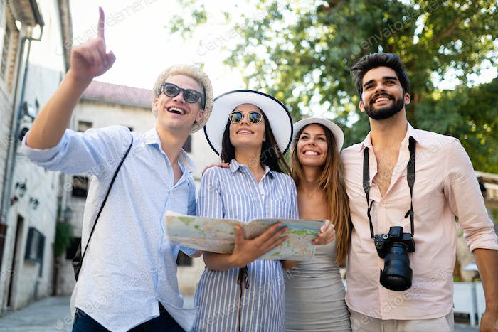 Young happy friends tourists sightseeing in city at summer