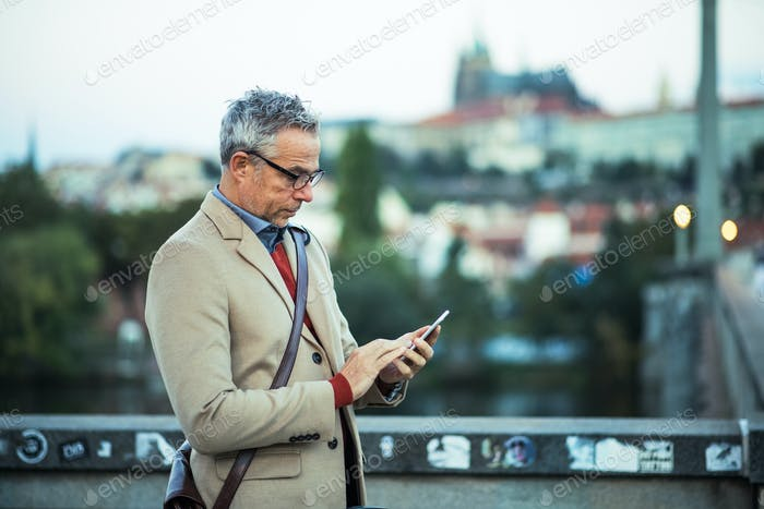 Businessman with smartphone standing on a bridge in city, text messaging.