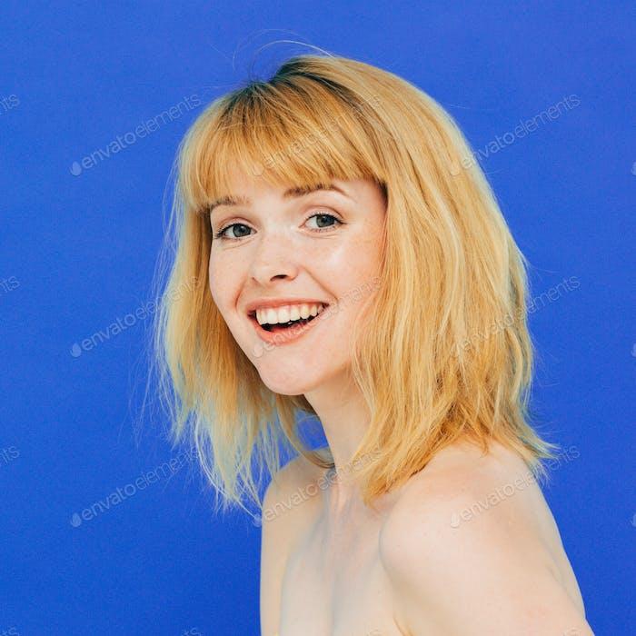 Schöne Frau Emotion Porträt rot blonde Haare auf blauem Hintergrund