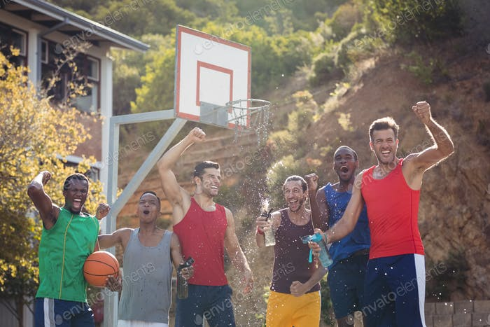 Basketball players celebrating by splashing water on each other
