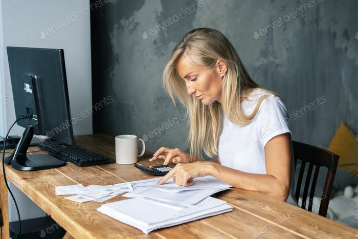 Young business woman sitting at a desk counts on a calculator bills and amounts. Financial literacy