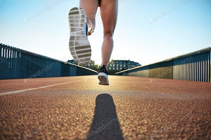 Bare legged jogger bounds towards apartments