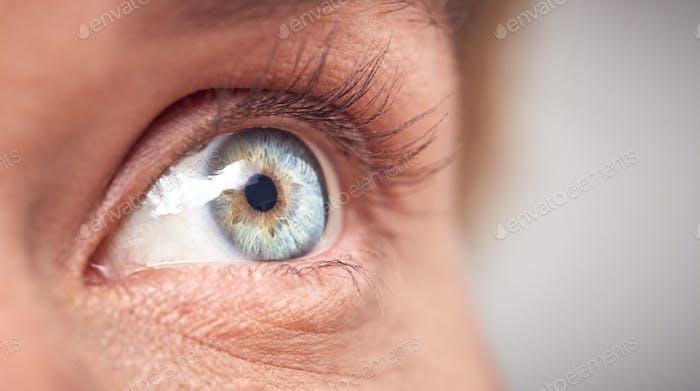 Extreme Nahaufnahme von Auge der Frau vor Weiß Studio Hintergrund