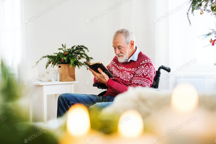 A senior man in wheelchair reading a book at home at Christmas time.