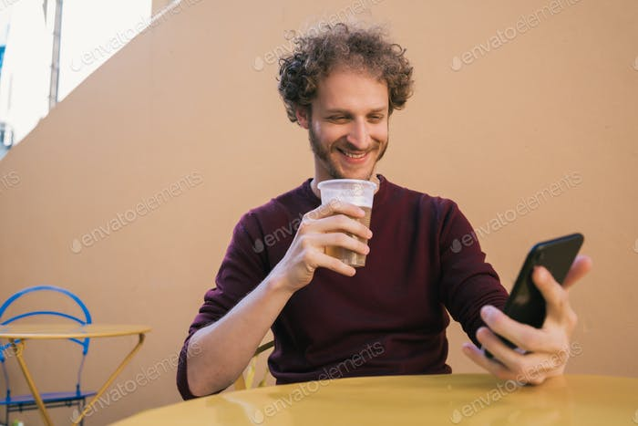 Man using his mobile phone while drinking beer.