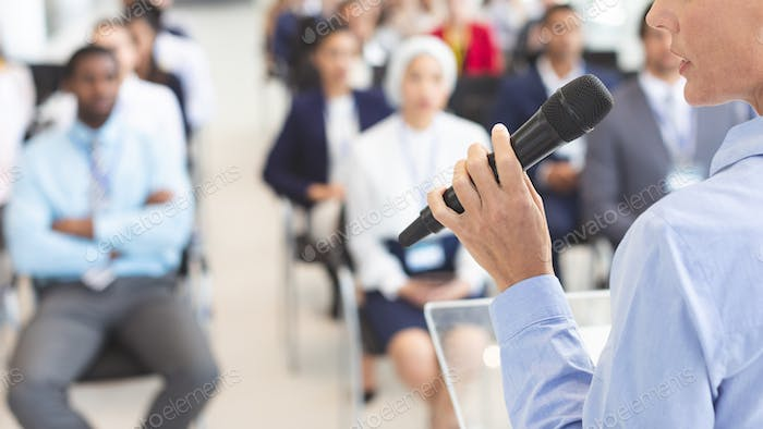Female speaker speaks to diverse business people in business seminar in conference room