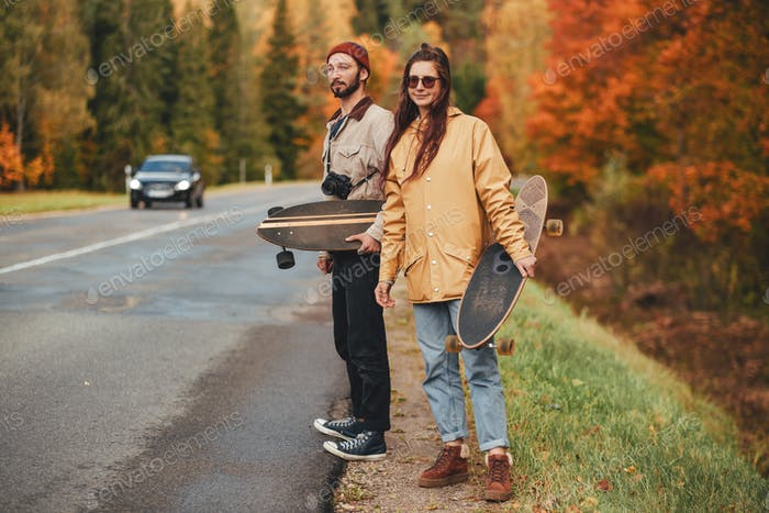 Couple of girl and guy hitchhiking in autumn forest