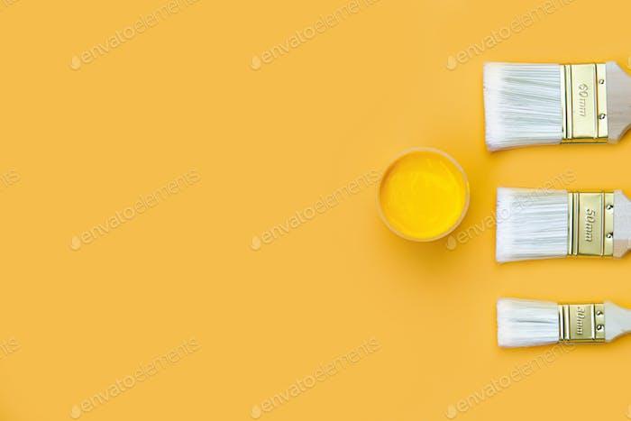 Lazo de pintura y pincel sobre fondo naranja.